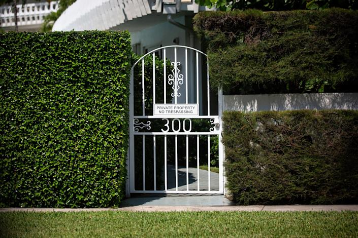 A large hedge and a gate with a no-trespassing sign obscures the view of a large home in Palm Beach.
