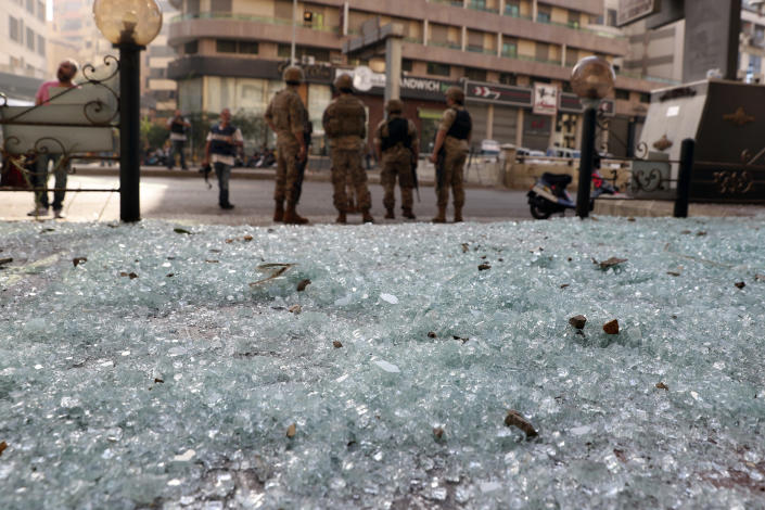 Glass from broken windows litters a street as Lebanese army soldiers stand guard after deadly clashes erupted along a former 1975-90 civil war front-line between Muslim Shiite and Christian areas, in Ain el-Remaneh neighborhood, Beirut, Lebanon, Thursday, Oct. 14, 2021. Lebanese officials say at least six people were killed and dozens were wounded in armed clashes that erupted in Beirut during protests organized by the militant Hezbollah group and its allies against the lead investigator into last year's massive blast at the city's port. (AP Photo/Bilal Hussein)