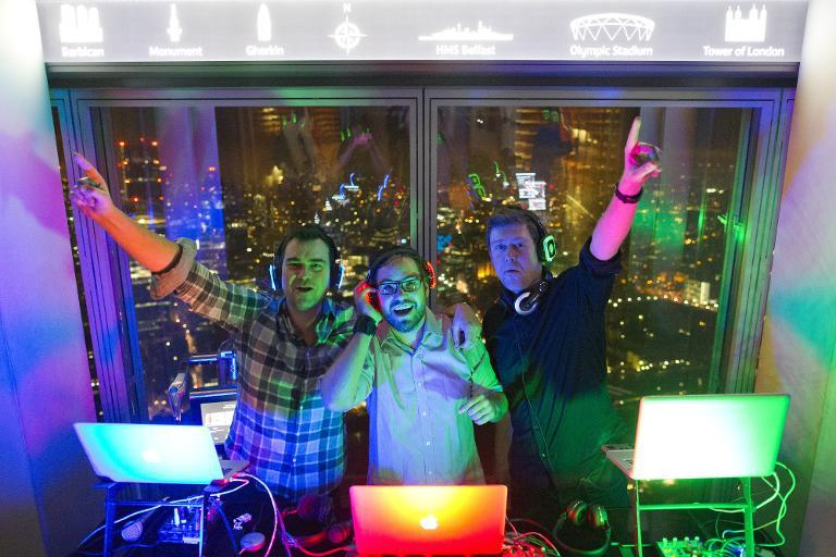 Three DJs playing three different types of music are seen at a silent disco at the 'Shard' tower, on the south bank of the river Thames in central London, on November 15, 2014 (AFP Photo/Justin Tallis)