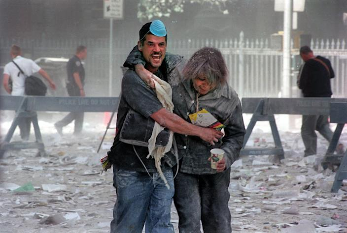 A man supports a woman as they walk through the rubble on 9/11.