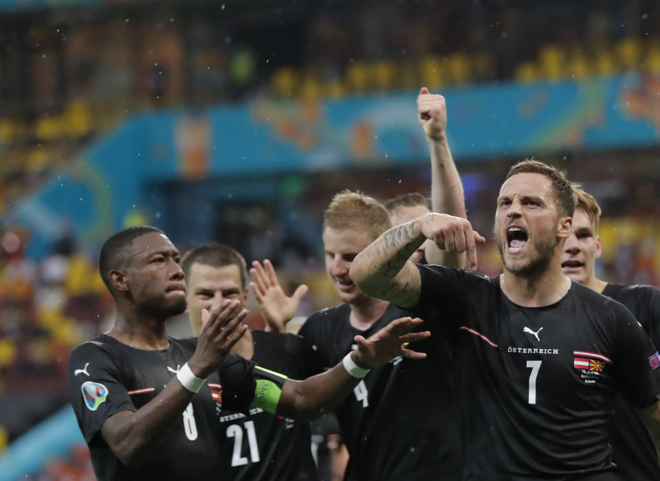 Austria's Marko Arnautovic, right, celebrates with teammates after scoring his side's third goal during the Euro 2020 soccer championship group C match between Austria and Northern Macedonia at the National Arena stadium in Bucharest, Romania, Sunday, June 13, 2021. (Robert Ghement/Pool via AP)