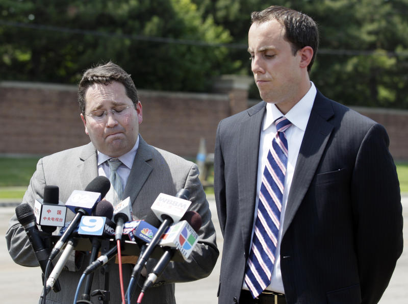 Attorneys Erron Fisher, left, and Michael LaMonica pause during a news conference on Friday, July 6, 2012, in Northbrook, Ill. The attorneys represent the sons of Burton and Zorine Lindner, of Glenview, Ill., who were killed Wednesday, July 4, 2012, during a freight train derailment. The couple were driving under a railroad bridge when the train derailed. Twenty-eight rail cars hauling coal piled up on the bridge, causing it to collapse over a road between the suburbs of Glenview and Northbrook. A huge mound of twisted train cars and coal filled the gap where the bridge had been. (AP Photo/Nam Y. Huh)