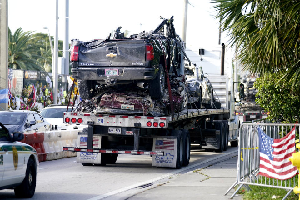 Damaged vehicles are transported from the rubble of the Champlain Towers South building, as removal and recovery work continues at the site of the partially collapsed condo building, Tuesday, July 13, 2021, in Surfside, Fla. (AP Photo/Lynne Sladky)
