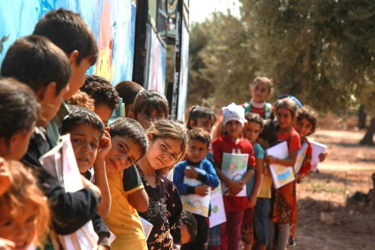 Displaced Syrian children queue for their turn outside a bus converted into a classroom in Idlib in September 2019 (AFP Photo/Aaref WATAD)