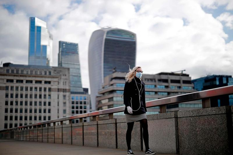 A woman wearing PPE walks in London (AFP via Getty Images)