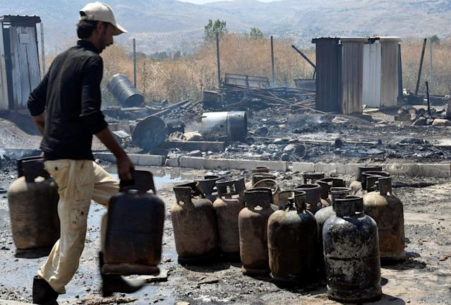 <p>A man moves gas canisters after a fire tore through a camp for Syrian refugees, near the town of Qab Elias, in Lebanon's Bekaa Valley, July 2, 2017. (Hassan Abdallah/Reuters) </p>