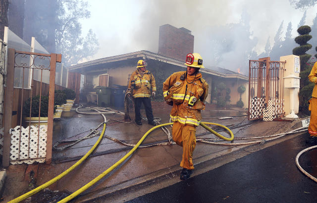 <p>Los Angeles firefighters battle to contain flames to a home on fire and prevent the fire's spread to adjoining properties in the Bel Air district of Los Angeles Wednesday, Dec. 6, 2017. (Photo: Reed Saxon/AP) </p>