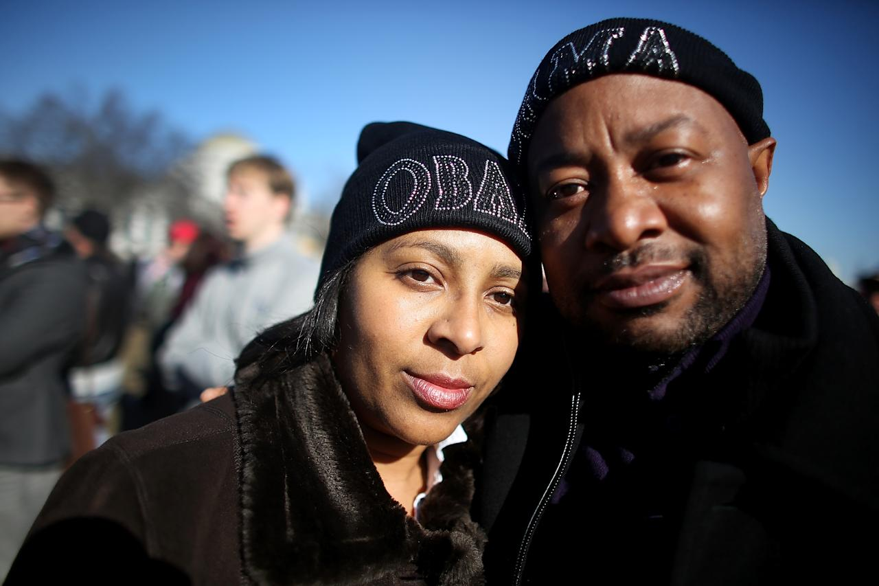 WASHINGTON, DC - JANUARY 20:  Obama supporters Teresa Thomason and Charles Walker pose with their Obama hats as Washington prepares for President Barack Obama's second inauguration on January 20, 2013 in Washington, DC. One day before the public inaugural ceremony at the U.S. Captiol on January 21, Obama was officially sworn in for his second term during a private ceremony surrounded by friends and family in the Blue Room of the White House.  (Photo by Mario Tama/Getty Images)