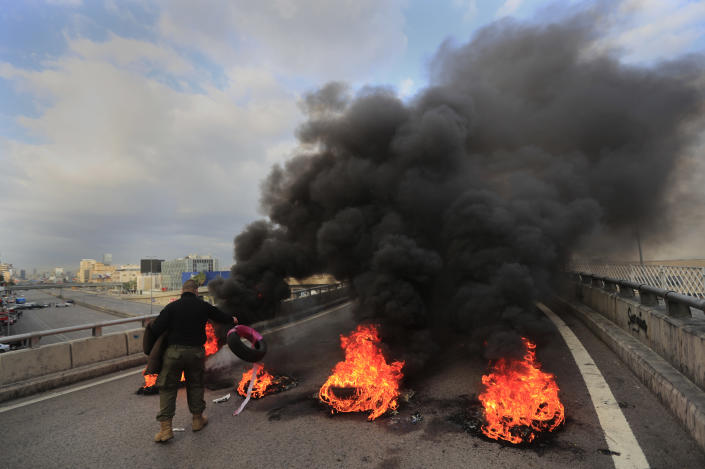 A protester burns tires to block a main highway, during a protest in the town of Jal el-Dib, north of Beirut, Lebanon, Monday, March 8, 2021. The dayslong protests intensified Monday amid a crash in the local currency, increase of consumer goods prices and political bickering between rival groups that has delayed the formation of a new government. (AP Photo/Hussein Malla)