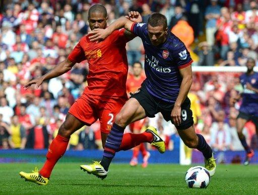 Arsenal's German forward Lukas Podolski (right) vies with Liverpool defender Glen Johnson during the Premier League match between Liverpool and Arsenal at Anfield in Liverpool. Arsenal ended their goal drought in emphatic fashion as Podolski and Santi Cazorla inspired an impressive 2-0 win at Liverpool