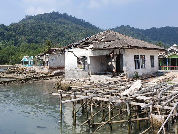 Damaged buildings on a seafront, tropical forest background.