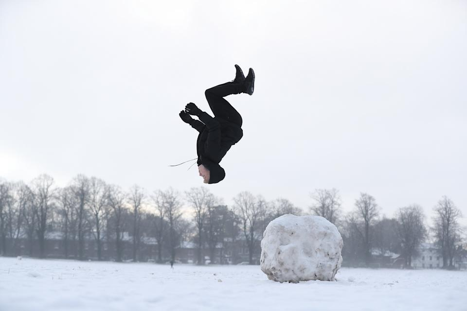 Jack Austin does a backflip off a snowball on Knutsford Heath in Cheshire. (PA)