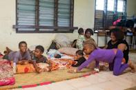A Fijian family takes refuge in a temporary shelter during super cyclone Yasa in the capital city of Suva on December 17, 2020