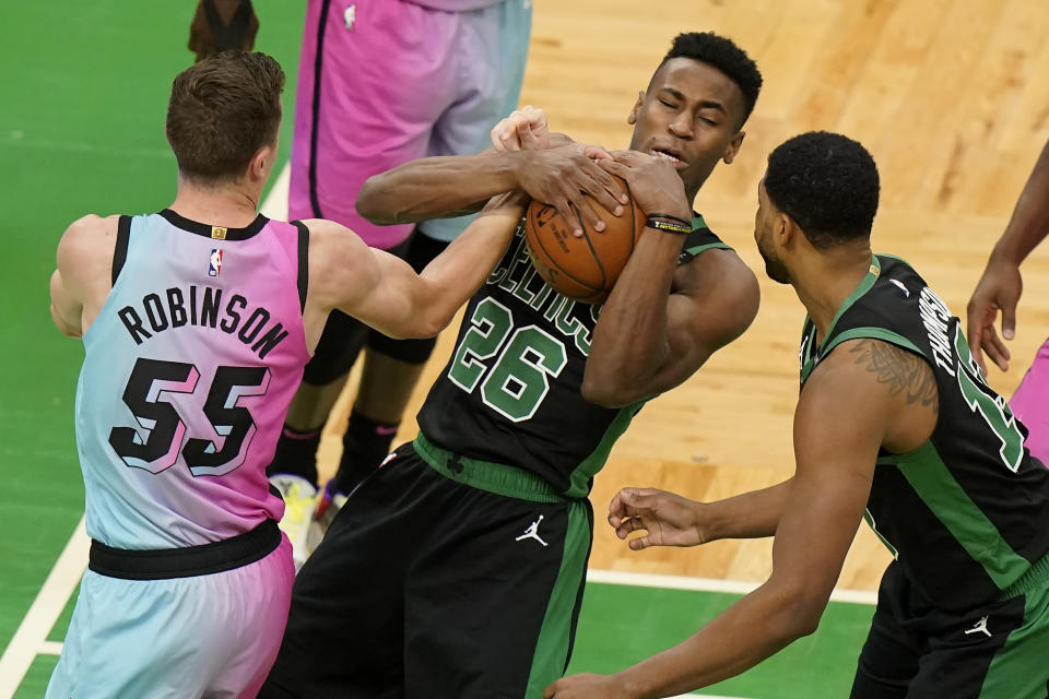 Boston Celtics' Aaron Nesmith (26) vies for control the ball with Miami Heat's Duncan Robinson (55) as Celtics' Tristan Thompson, right, looks on in the first half of a basketball game, Sunday, May 9, 2021, in Boston. (AP Photo/Steven Senne)