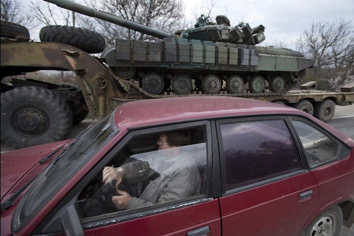 A man drives his car as Ukrainian tanks are transported from their base in Perevalnoe, outside Simferopol, Crimea, Wednesday, March 26, 2014. Ukraine has started withdrawing its troops and weapons from Crimea, now controlled by Russia. (AP Photo/Pavel Golovkin)