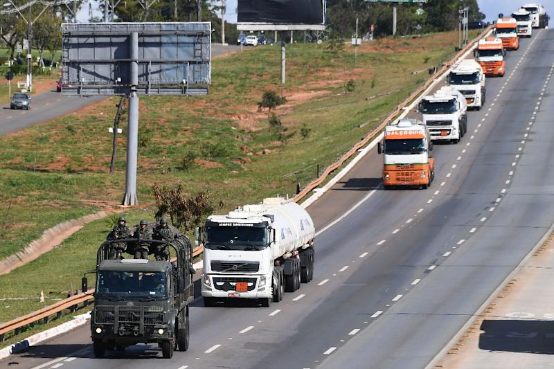 A convoy of trucks carrying aviation fuel is escorted by the army to supply airports in Brasilia (AFP Photo/EVARISTO SA)