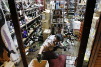 A liquor shop's manager clears the damaged bottles following an earthquake in Fukushima, northeastern Japan Saturday, Feb. 13, 2021. The Japan Meteorological Agency says a strong earthquake has hit off the coast of northeastern Japan, shaking Fukushima, Miyagi and other areas. (Jun Hirata/Kyodo News via AP)