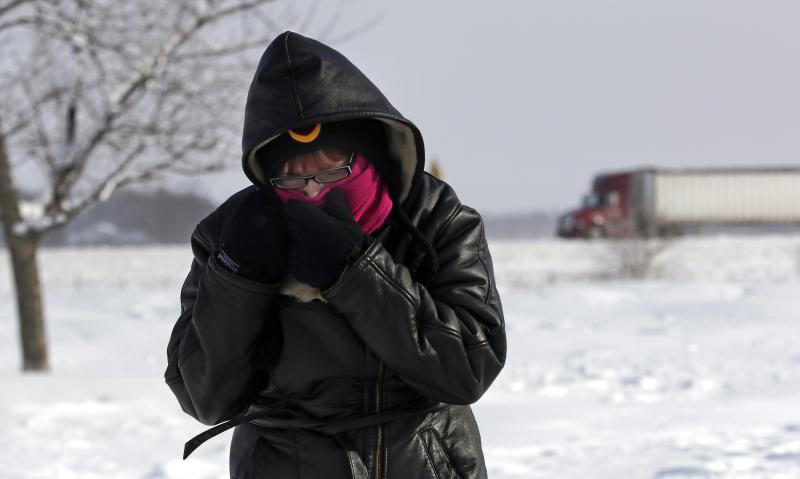 Megan Draper of Noblesville, Indiana covers her face to stay warm north of Indianapolis, Indiana