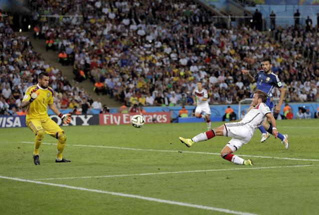 Germany's Mario Goetze kicks to score his side's first goal in extra time against Argentina's goalkeeper Sergio Romero during the World Cup final soccer match between Germany and Argentina at the Maracana Stadium in Rio de Janeiro, Brazil, Sunday, July 13, 2014. (AP Photo/Felipe Dana)