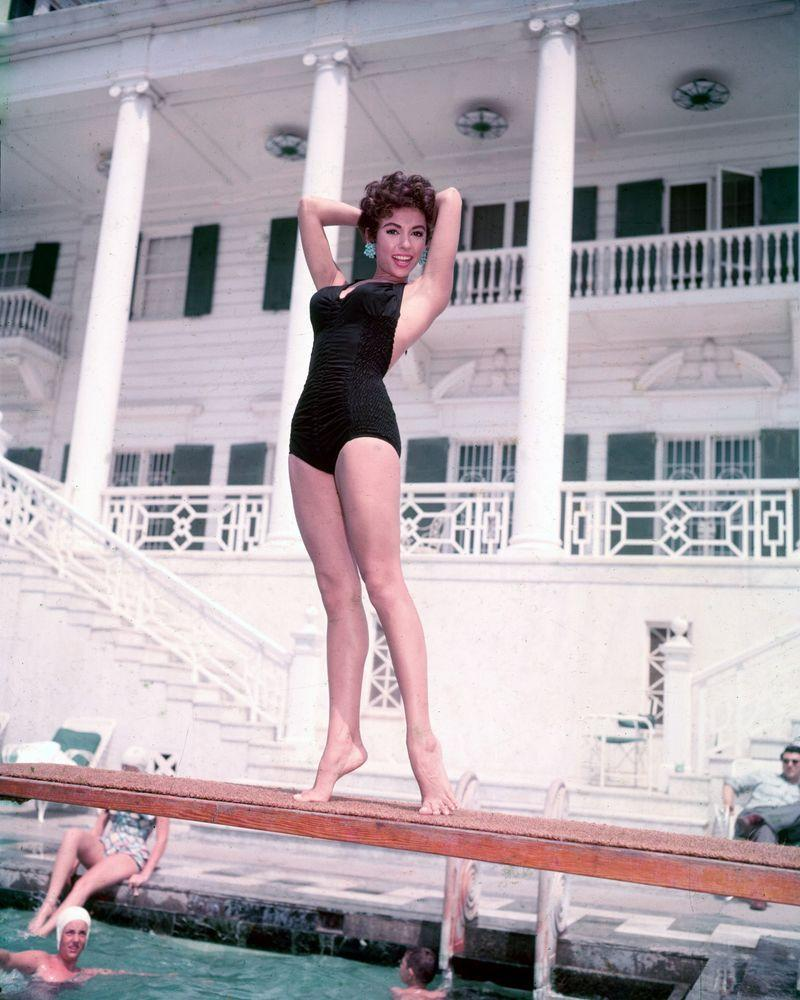 <p>Rita Moreno looks chic in a black one-piece swimsuit as she poses on a diving board in 1955.</p>