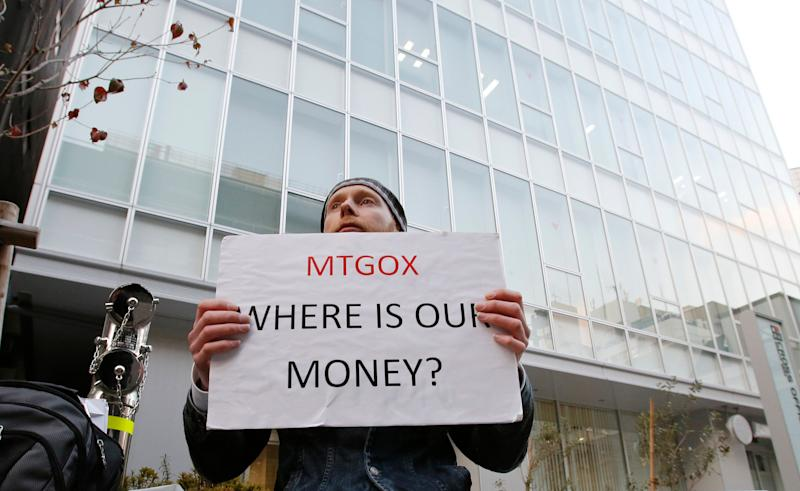 Kolin Burges, a self-styled cryptocurrency trader and former software engineer who came from London, holds a placard to protest against Mt. Gox, in front of the building where the digital marketplace operator is housed in Tokyo February 25, 2014. The website of Mt. Gox appears to be taken down, shortly after six major Bitcoin exchanges released a joint statement distancing themselves from the troubled Tokyo-based bitcoin exchange. Tokyo-based Mt. Gox was a founding member and one of the three elected industry representatives on the board of the Bitcoin Foundation. REUTERS/Toru Hanai (JAPAN - Tags: BUSINESS CIVIL UNREST SCIENCE TECHNOLOGY)