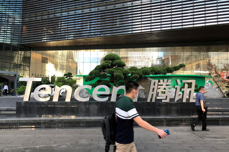 FILE PHOTO: People walk past a Tencent sign at the company headquarters in Shenzhen