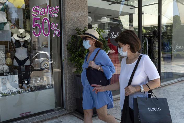 Two women walk at a commercial street of Glyfada suburb, near Athens, on Saturday, Aug. 1, 2020. Greek authorities introduced tougher restrictions this week following an increase in coronavirus infections, most unrelated to tourism. (AP Photo/Yorgos Karahalis)