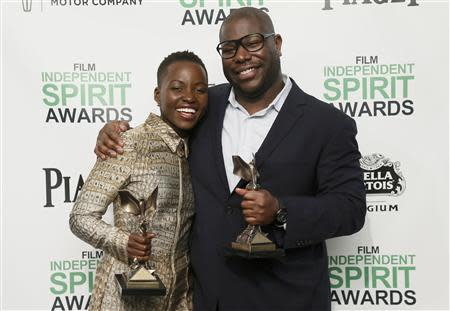 """Actress Lupita Nyong'o and director Steve McQueen pose with their awards for """"12 Years a Slave"""" backstage at the 2014 Film Independent Spirit Awards in Santa Monica, California March 1, 2014. REUTERS/Danny Moloshok"""