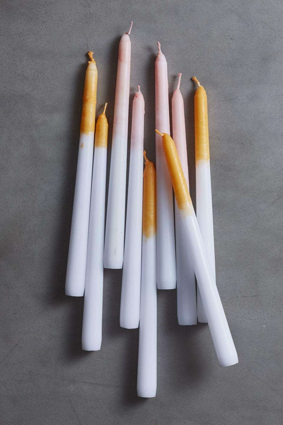 """<p>Up for a fairly easy DIY candle project? Begin by shaving orange crayons into melted max. Stir and then dip white candlesticks into the mixture. Place them in your favorite candleholders once they're all dry. </p><p><a class=""""link rapid-noclick-resp"""" href=""""https://www.target.com/p/10-12pk-unscented-taper-candles-white-made-by-design-8482/-/A-54013258"""" rel=""""nofollow noopener"""" target=""""_blank"""" data-ylk=""""slk:SHOP WHITE CANDLES"""">SHOP WHITE CANDLES</a></p>"""