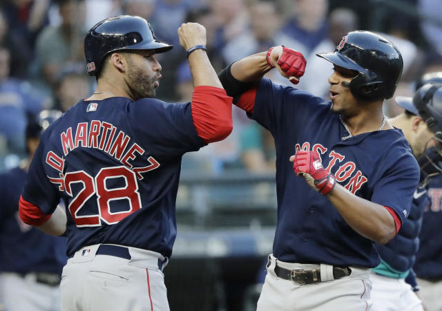 Boston Red Sox's Xander Bogaerts, right, is greeted by J.D. Martinez (28) after Bogaerts hit a three-run home run during the third inning of a baseball game against the Seattle Mariners to score Martinez and Mitch Moreland, Friday, June 15, 2018, in Seattle. (AP Photo/Ted S. Warren)