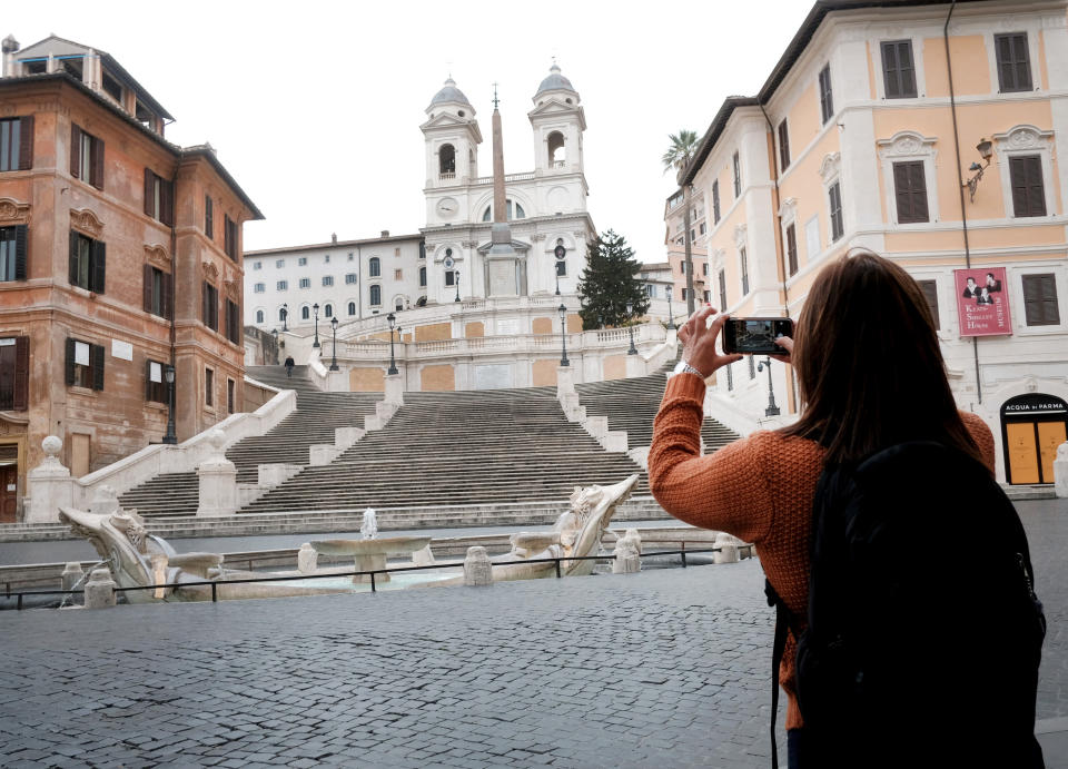 A woman takes photos of The Spanish Steps in Rome Friday, March 13, 2020. A sweeping lockdown is in place in Italy to try to slow down the spread of coronavirus epidemic. For most people, the new coronavirus causes only mild or moderate symptoms. For some, it can cause more severe illness, especially in older adults and people with existing health problems. (Mauro Scrobogna/LaPresse via AP)