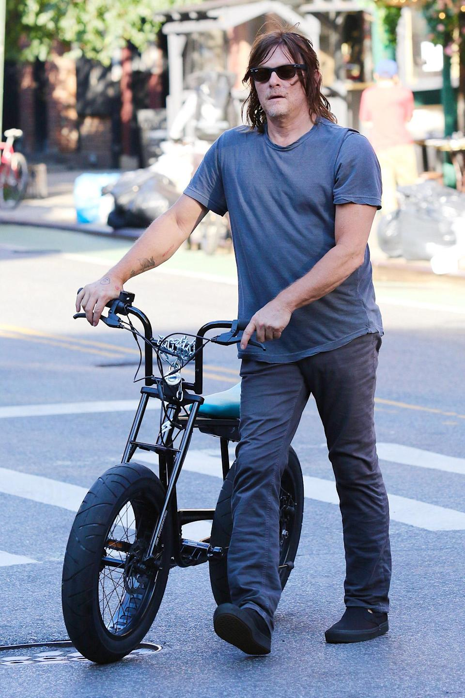<p>Norman Reedus walks home after taking a bike ride through downtown N.Y.C. on July 31.</p>