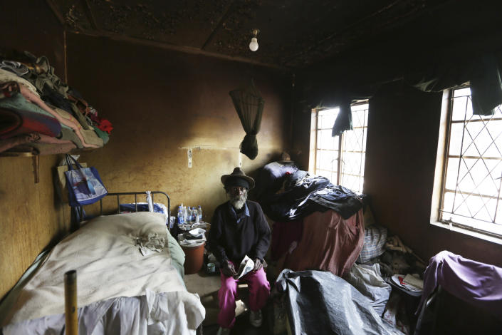 An elderly man sits inside his room at the Society for the Destitute Aged care home in Harare's Highfield township, Zimbabwe, Thursday June 24, 2021. The economic ravages of COVID-19 are forcing some families in Zimbabwe to abandon the age old tradition of taking care of the elderly. Zimbabwe's care homes have experienced a 60% increase in admissions since the outbreak of the pandemic in March last year. (AP Photo/Tsvangirayi Mukwazhi)