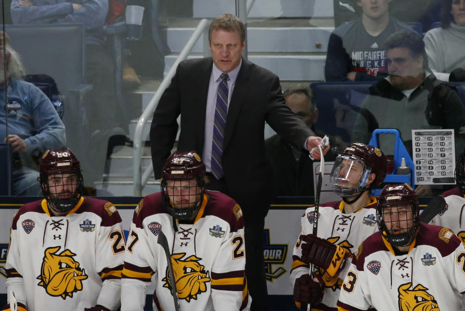 FILE - In this Saturday, April 13, 2019 file photo, Minnesota-Duluth coach Scott Sandelin stands behind players during the second period of the team's NCAA Frozen Four men's college hockey championship game against Massachusetts in Buffalo, N.Y. The NCAA men's hockey tournament bracket this year would have made Herb Brooks proud. For the first time, all five Division I programs from Minnesota made the 16-team field. Minnesota is the No. 3 overall seed. (AP Photo/Jeffrey T. Barnes, File)