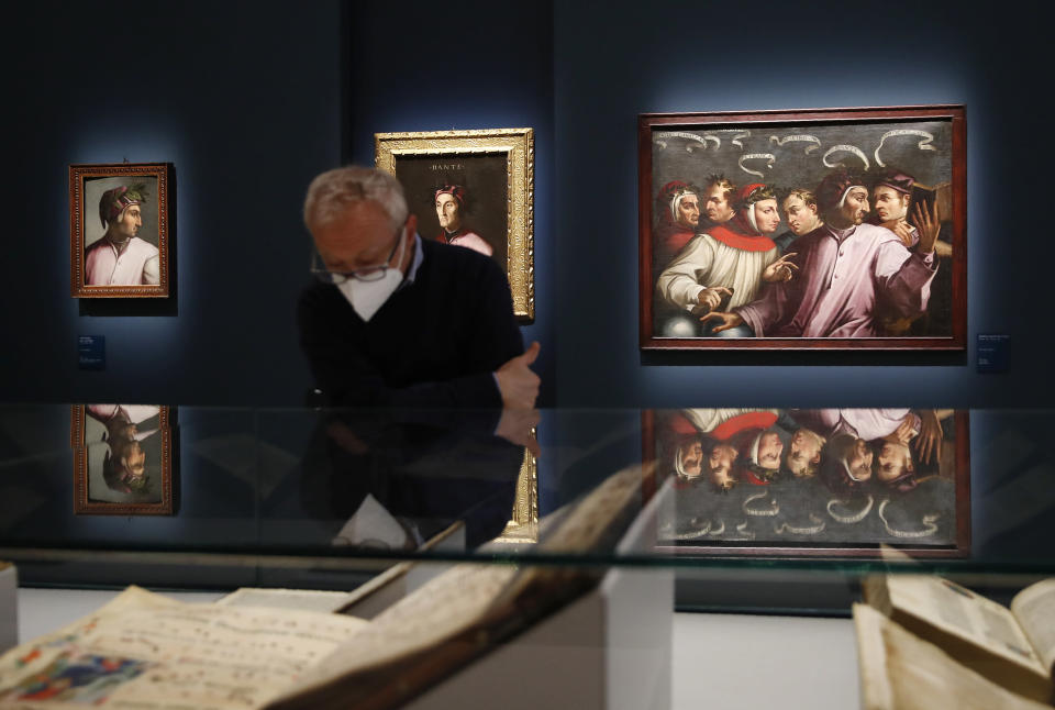 """A man looks at ancient books on display at the """"Dante. La visione dell'arte"""" (Dante. The Vision of Art) exhibition, in Forli, Italy, Saturday, May 8, 2021. Italy is honoring its great poet Dante Alighieri in myriad ways on the 700th anniversary of his death, with new musical scores and gala concerts, exhibits and dramatic readings against stunning backgrounds in every corner of the land. (AP Photo/Antonio Calanni)"""