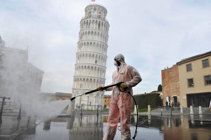 """A worker sanitizes the Piazza dei Miracoli near to the Tower of Pisa in Pisa, Italy, on March 17 2020. <p class=""""copyright"""">Laura Lezza/Getty Images</p>"""