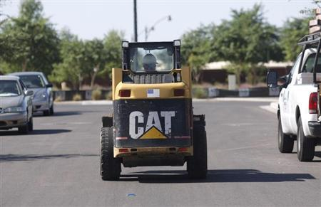 A worker drives a Caterpillar tractor near a construction site in Gilbert