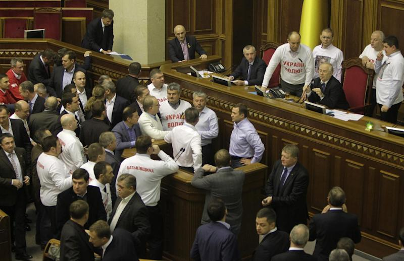Opposition lawmakers block the podium in Ukraine's parliament in Kiev, Ukraine, Friday, Nov. 22, 2013. Opposition lawmakers on Friday booed Ukraine's prime minister, whose government shelved a landmark deal with the European Union, while turning toward Moscow. (AP Photo/Sergei Chuzavkov)