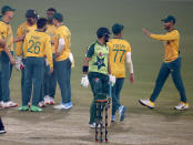 Pakistan's Hussain Talat, center, walks back to pavilion while South Africa player celebrate his dismissal during the 1st Twenty20 cricket match between Pakistan and South Africa at the Gaddafi Stadium, in Lahore, Pakistan, Thursday, Feb. 11, 2021. (AP Photo/K.M. Chaudary)