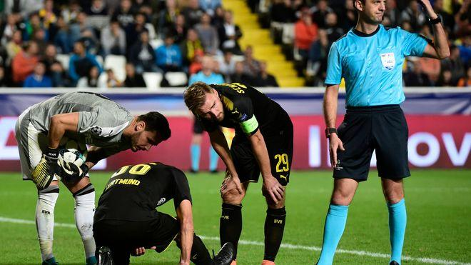 Belarusian referee Aleksei Kulbakov (R) calls for medical assistance as Dortmund's German defender Marcel Schmelzer (2nd-R) and Swiss goalkeeper Roman Burki (L) check up on injured Turkish defender Omer Toprak (2nd-L) during the UEFA Champions League football match between Apoel FC and Borussia Dortmund at the GSP Stadium in the Cypriot capital, Nicosia on October 17, 2017. / AFP PHOTO / KHALED DESOUKI (Photo credit should read KHALED DESOUKI/AFP/Getty Images)