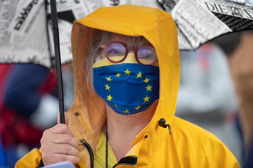 A member of a pro-European German association holds an umbrella on a footbridge over the Rhine river that links France to Germany, Sunday June 14, 2020 in Strasbourg, eastern France. The majority of European countries will be reopening Monday June 15, 2020 their borders and lifting the restrictions that had been in place during the COVID-19 pandemic. (AP Photo/Jean-Francois Badias)