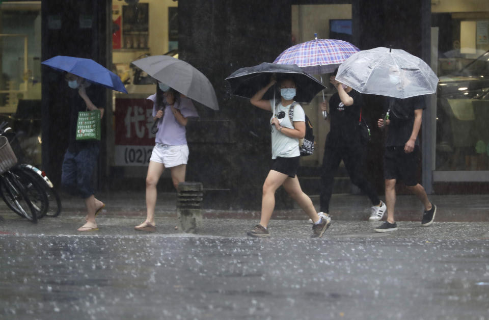 People walk in the rain caused by Typhoon Chanthu in Taipei, Taiwan, Sunday, Sept. 12, 2021. Typhoon Chanthu drenched Taiwan with heavy rain Sunday as the storm's center passed the island's east coast heading for Shanghai. (AP Photo/Chiang Ying-ying)