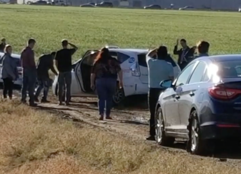 Photo of drivers standing outside their cars stuck in mud on the way to Denver International Airport.
