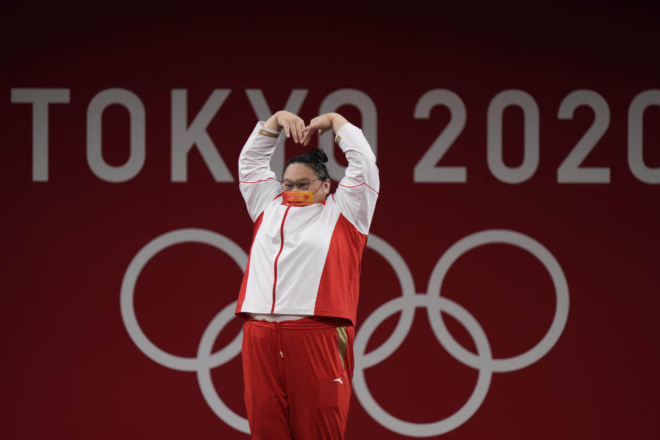 Li Wenwen of China makes a heart with her hands as she takes the podium to receive the gold medal in the women's +87kg weightlifting at the 2020 Summer Olympics, Monday, Aug. 2, 2021, in Tokyo, Japan. (AP Photo/Luca Bruno)