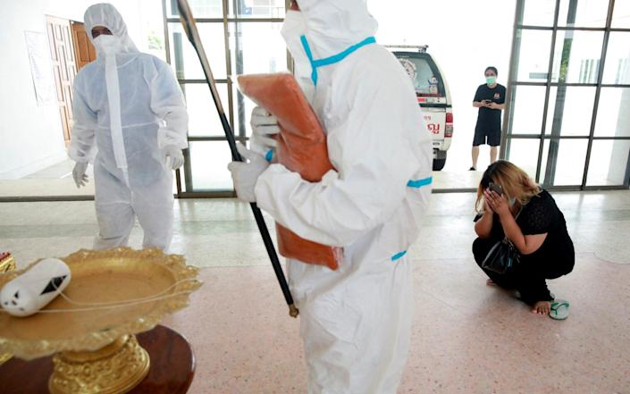 AA family member cries as Thai Buddhist monk Pongpetch Santijittho is seen wearing a protective suit over his robe to cremate the body of a coronavirus disease (COVID-19) victim at a temple in Pathumthani Province, near Bangkok, Thailand July 15, 2021. - Reuters