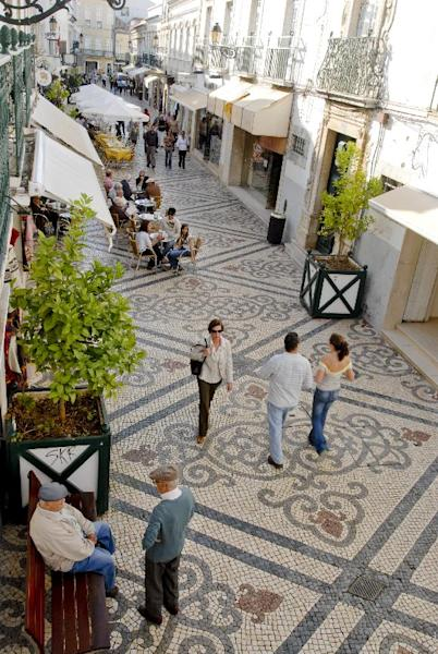 This undated image provided by the Portuguese National Tourist Office shows pedestrians, shoppers and diners in Faro, on Portugal's southern coast. The charming walkways are tiled in intricate patterns. Faro's other attractions include beaches and a historic walled town. (AP Photo/Associacao Turismo do Algarve/Portuguese National Tourist Office, Luís da Cruz)