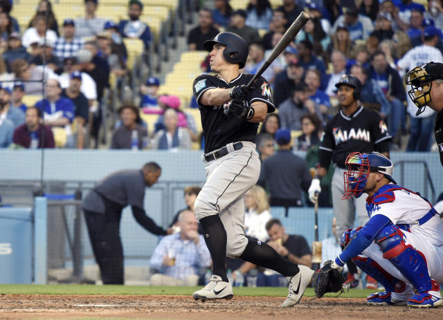 Miami Marlins' J.T. Realmuto, left, hits a solo home run as Los Angeles Dodgers catcher Yasmani Grandal, center, and home plate umpire Joe West watch during the sixth inning of a baseball game Wednesday, April 25, 2018, in Los Angeles. (AP Photo/Mark J. Terrill)