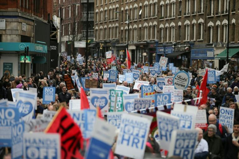 Protesters march with banners and placards against private companies' involvement in the National Health Service (NHS) and social care services provision and against cuts to NHS funding in central London on March 4, 2017
