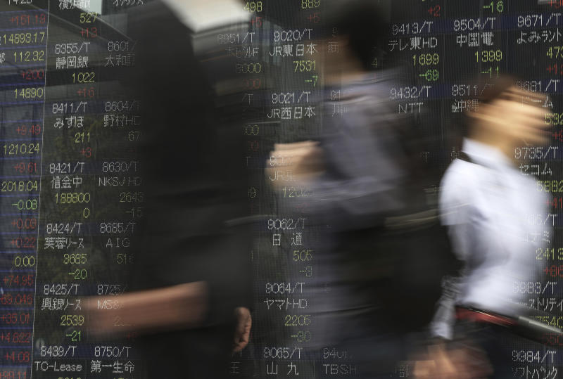 People walk past an electronic stock board of a securities firm in Tokyo, Wednesday, April 2, 2014. Asian stock markets pushed higher Wednesday on signs of a pickup in the U.S. economy and expectations of further stimulus in Japan. Tokyo's Nikkei 225 closed at 14,946.32, after gaining 154.33 points, or 1.04 percent. (AP Photo/Eugene Hoshiko)