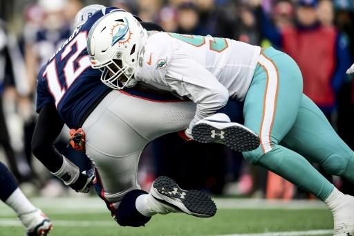 Shocker: New England quarterback Tom Brady is sacked by Miami's Trent Harris in the Dolphins' upset win over the Patriots on the final day of the 2019 NFL regular season